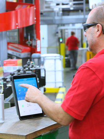 Men checking production process on tablet
